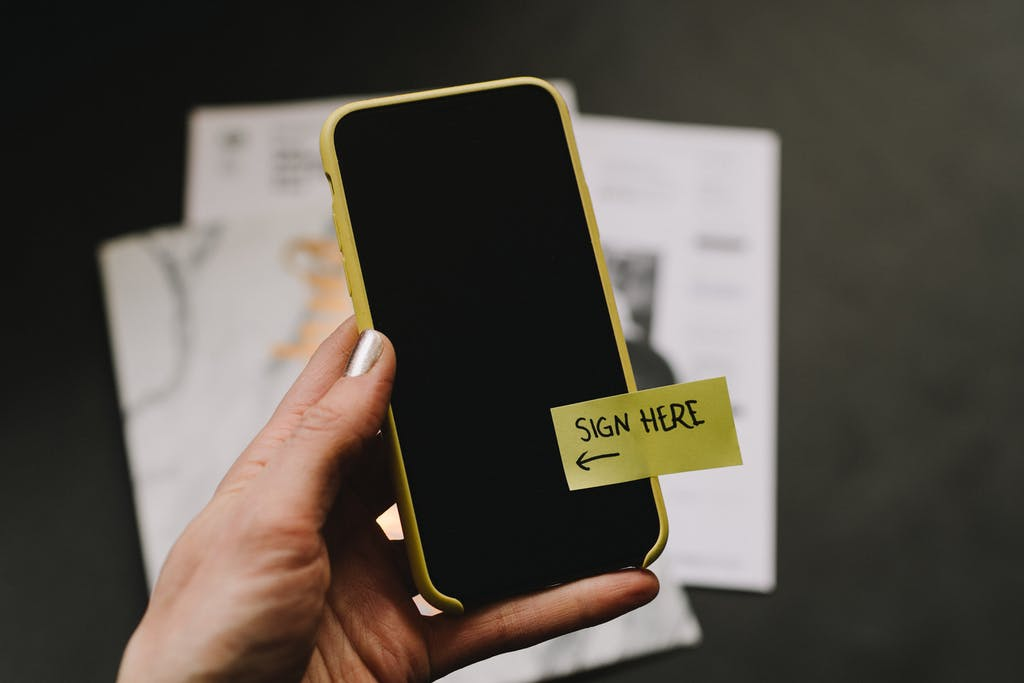 Cell phone with a sticky note that says sign here