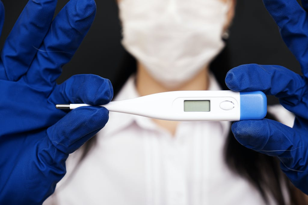 Doctor holding a thermometer