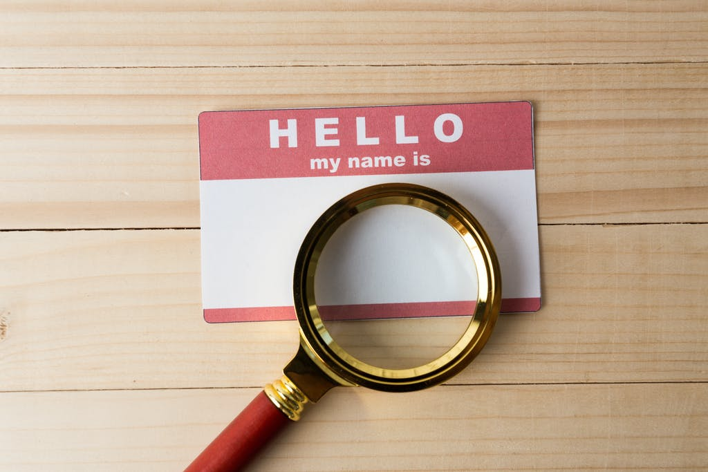 Hello name tag and a magnifying glass