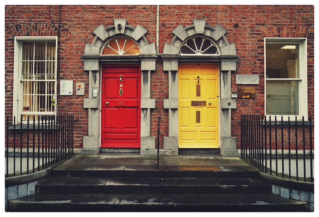 House with a red door next to a house with a yellow door